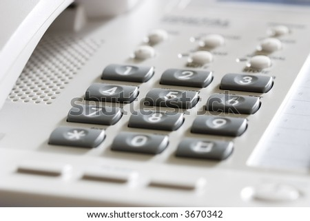 White office desk phone close-up. Focus on the center button