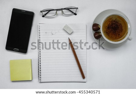 White office desk table with laptop, pencil, and a cup of coffee. Top view with copy space.