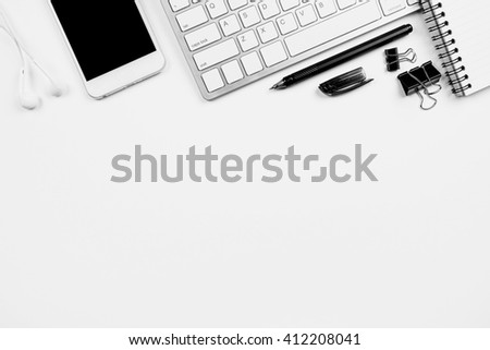White office desk with computer keyboard, smartphone and other office supplies. Top view with copy space. - stock photo