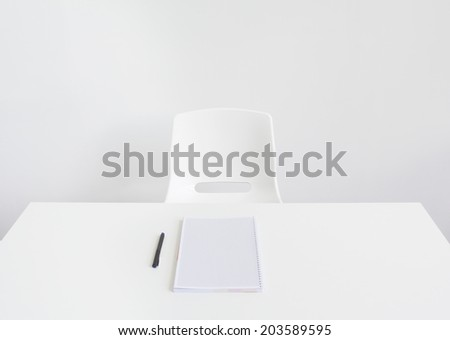 White office desk with notebook and pen - stock photo