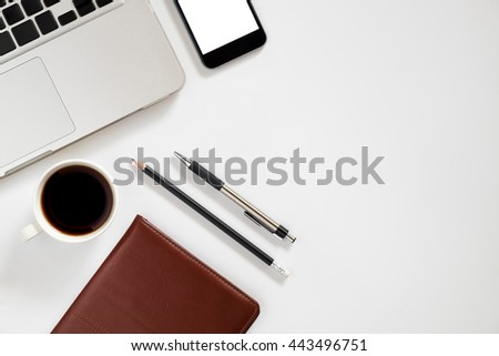 White office workspace with blank screen smartphone, leather notebook, pen, pencil, laptop and cup of coffee. Top view with copy space - stock photo