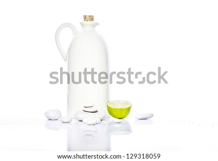 White oil bottle with white stones and citrus near