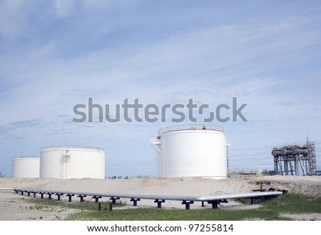 White oil reservoir. Oil and gas refinery plant. Industrial scene of oil field. Oil industry. Blue sky above grey sand. - stock photo