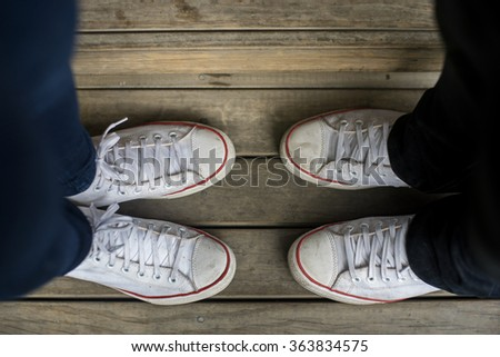 white old teenagers' shoes stand facing each other on wooden ground - stock photo