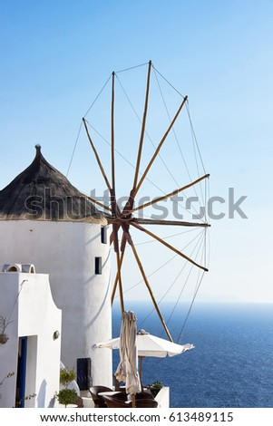 White old wimdmill on  background of blue sky and blue sea in the town of Oia,  Santorini island,  Greece,