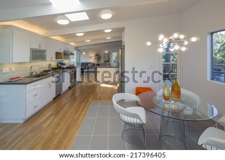 White open designer kitchen with fitting enthralling cabinets furniture and grey marble counter tops and modern sitting arrangement. - stock photo