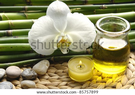 White orchid and stones with green grove and massage oil on wicker mat - stock photo