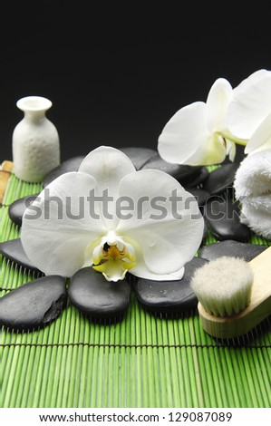 white orchid with pebble stone and towel on green mat
