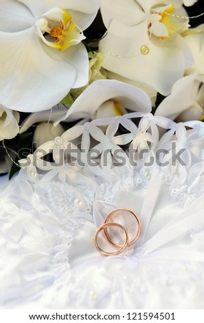 white orchids and wedding rings on bridal pillow - stock photo