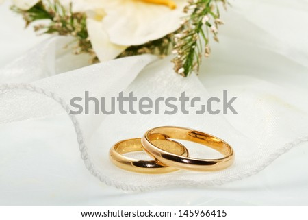 white orchids and wedding ringson white background