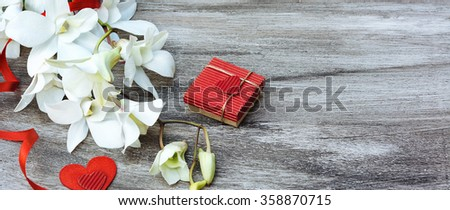 White orchids red ribbon, gift box and hearts on the grey wooden vintage background. Valentine card - stock photo