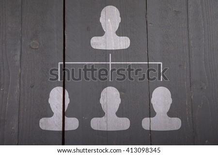 White organigram with white heads on dark black wooden background - stock photo