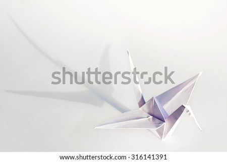 White origami crane isolated on white background with shadow. - stock photo