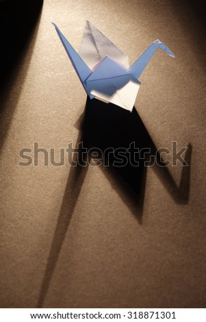 White origami crane isolated on wooden background with lights and shadows.