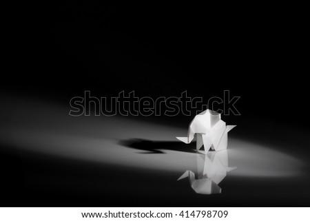 White origami elephant isolated on black background - stock photo