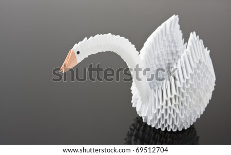 White origami swan on grey surface. Close-up view - stock photo