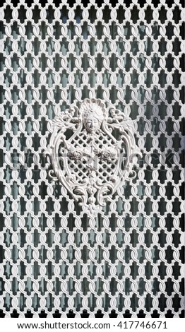 White ornamental grille with wrought pattern. - stock photo