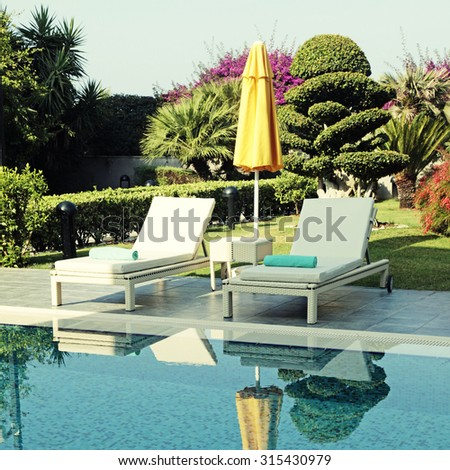 White outdoor furniture and yellow umbrella near the swimming pool for relax on summer resort. Square toned image