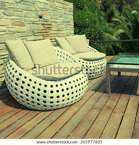 White outdoor furniture round rattan armchairs and glass table on wood resort terrace, Greece. Square toned image, instagram effect - stock photo