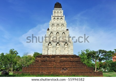 White pagoda with statues of standing Buddha inside.
