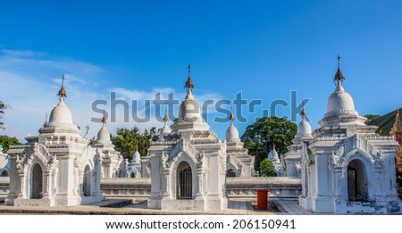 white pagodas in Kuthodaw temple with blue sky, Mandalay, Myanmar - stock photo