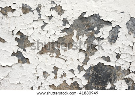 White paint on an exterior wall cracked and flaking to reveal old concrete beneath - stock photo