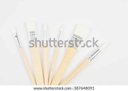 White paintbrushes with wooden handle, clear background
