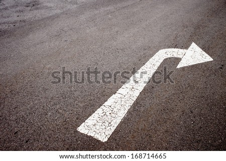 white painted arrow indicating left turn on tarmac surface