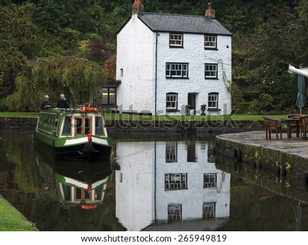 white painted house and reflection,on the Monmouthsire and Brecon Canal at Llanfoist Wharf,Wales.taken 15/10/2014 - stock photo