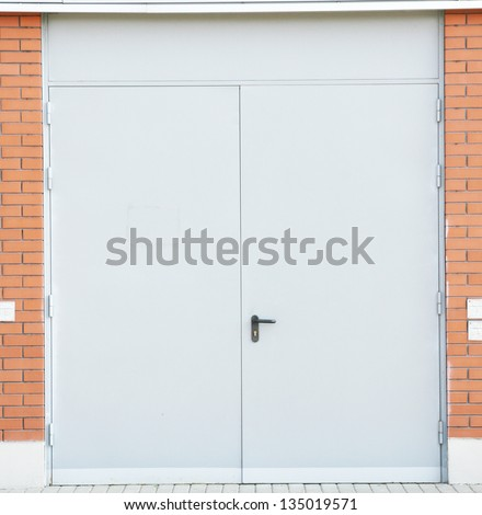 White painted metal door in a brick wall - stock photo