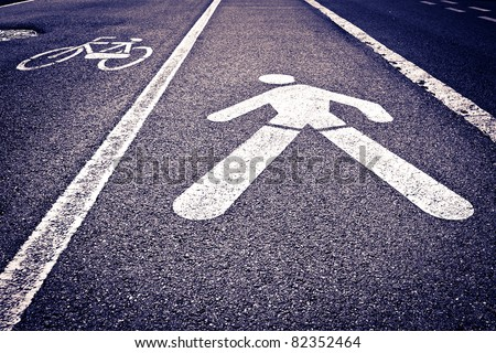 White painted sign indicating byke and pedestrian lanes. - stock photo