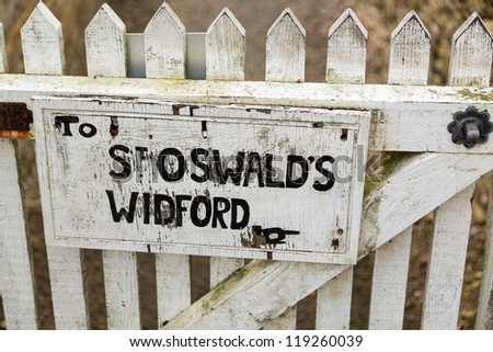 White painted sign to footpath to ancient church of St Oswald in Widford Oxford - stock photo