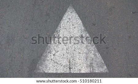 white painted triangle on asphalt road