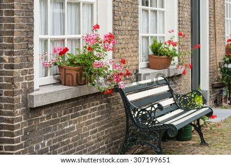 White painted window with lace curtain in a masonry wall. On the stone windowsill are pink and red flowering pelargonium plants in pots. Before the facade is a bench made from wrought iron and wood. - stock photo