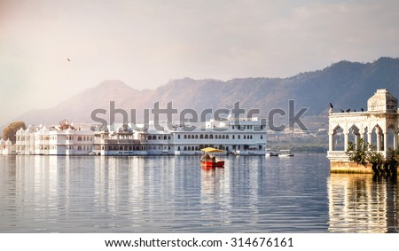 White palace and boat on Lake Pichola in Udaipur, Rajasthan, India - stock photo