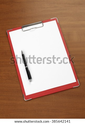 white paper and clipboard on wood background with pen