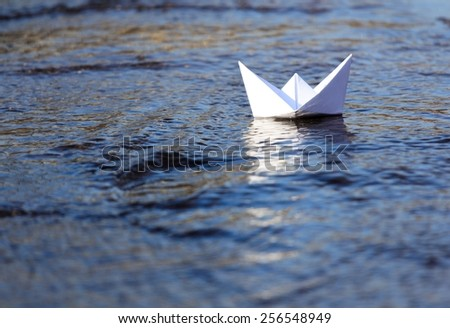 White Paper Boat Sailing on Blue Flowing Water  - stock photo