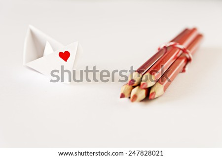 White paper boat with a red heart drawn on one side and a bunch of red color pencils - stock photo