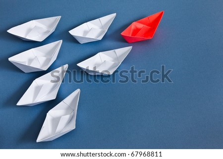White paper boats and one red boat.