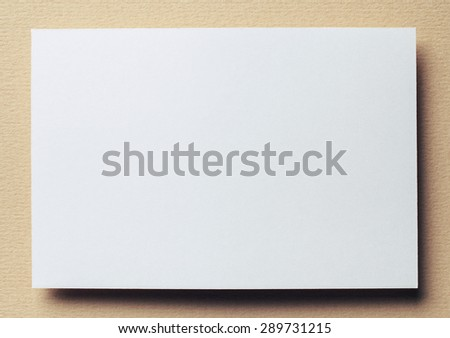 white paper card on beige background, place for tex