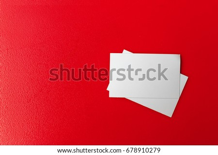 white paper card on red table with over light in the background