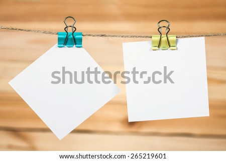 White paper cards hanging on a rope, on a wooden background. - stock photo