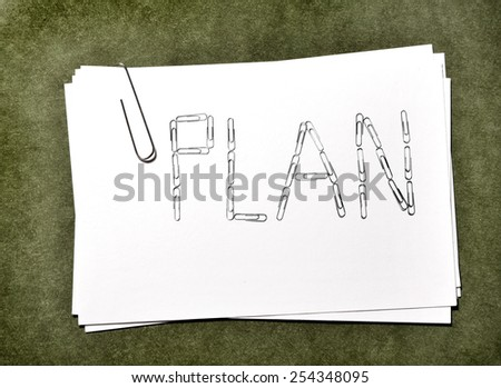 White paper cards with paperclip plan for business or school on green background - stock photo