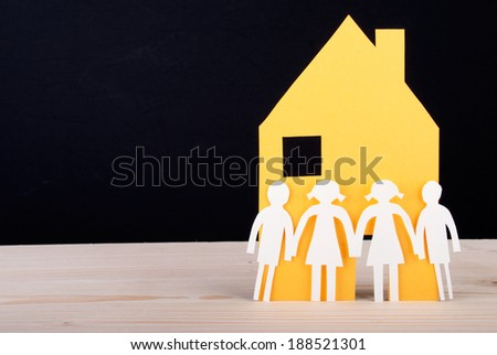 White Paper Chain Children in front of a Yellow Paper House, Black Background - stock photo