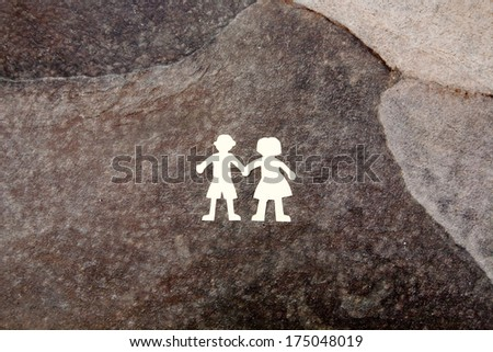 White paper couple silhouettes on the brown stone background