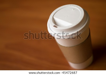 White paper cup of coffee on a wooden table. - stock photo