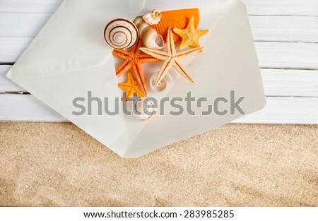 White paper envelope full of seashells on a wooden planks over sandy background. - stock photo