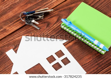 White paper house figure with notebook on wooden background. - stock photo
