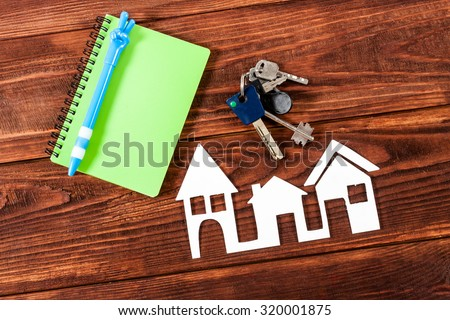 White paper house figure with notebook on wooden background.