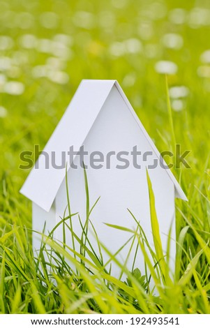 White paper house on green grass - real estate concept. - stock photo